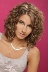 Medium Length Naturally Curly Brunette Hair With Side Part And Straightened Side Swept Fringe